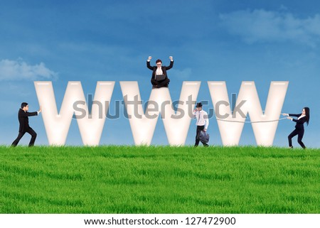 Business people using communication tools surround www letter on the green field - stock photo