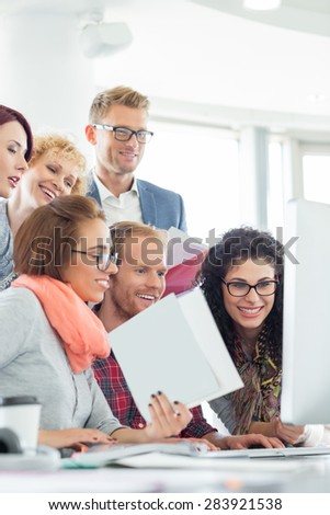 Business people using computer in creative office