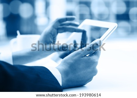 Business people using digital computer tablet concept, close up focus on hand with bokeh in blue tone. - stock photo