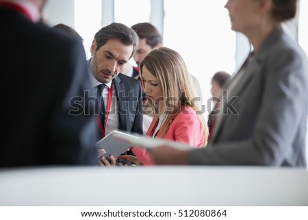 Business people using digital tablet in convention center