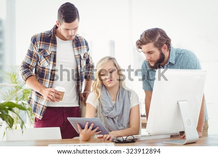 Business people using digital tablet while sitting at desk in office - stock photo