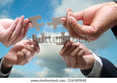 Business people using jigsaw puzzle for joy with team partnership  - stock photo