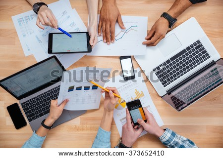 Business people using mobile phones and laptops, calculating and discussing charts and diagrams for financial report - stock photo
