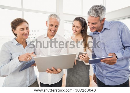 Business people using several electronic devices in the office