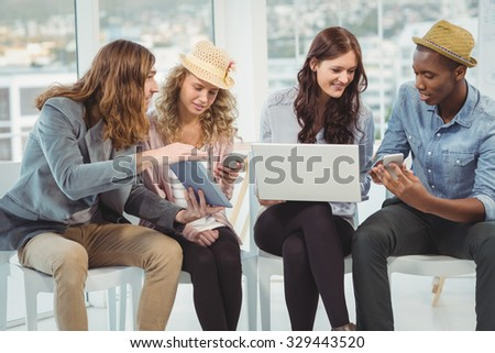 Business people using technology while discussing in creative office - stock photo