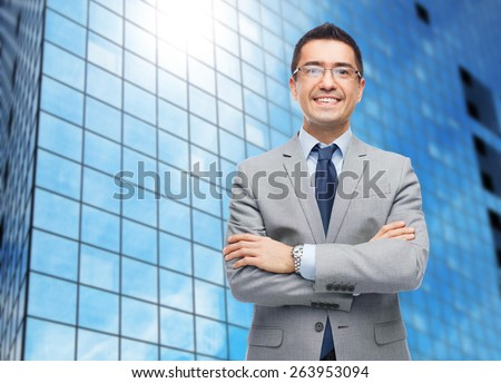 business, people, vision and office concept - happy smiling businessman in eyeglasses and suit over office building background - stock photo