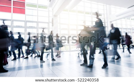 Business People Walking at Rush Hour on a traid fair flloor
