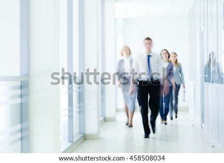 business people walking in the corridor of an business center, pronounced motion blur