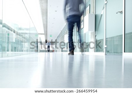 business people walking in the office corridor of an business center, pronounced motion blur Business people walking in the office corridor - stock photo