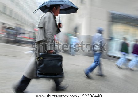business people walking in the street on a rainy day motion blurred