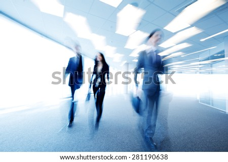 business people walking through office blurred - stock photo