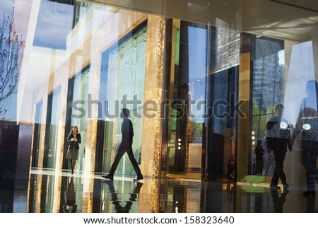 Business people walking through the lobby of an office  - stock photo