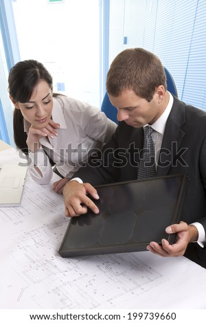 Business people wiht a small solar panel in the office - stock photo