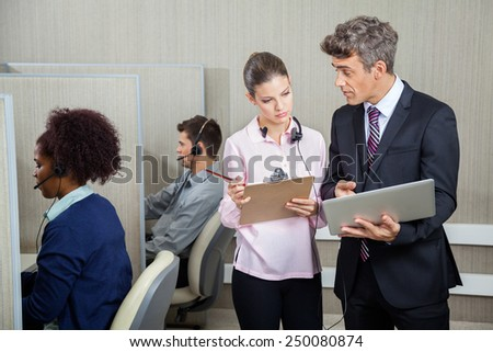 Business people with clipboard and laptop discussing while employees working in office