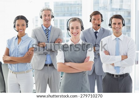 Business people with headsets smiling at camera in office - stock photo