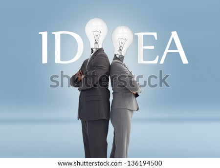 Business people with light bulb heads and idea text posing against blue background - stock photo