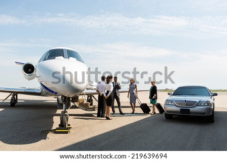 Business people with pilot and airhostess standing near private jet and limo at terminal - stock photo