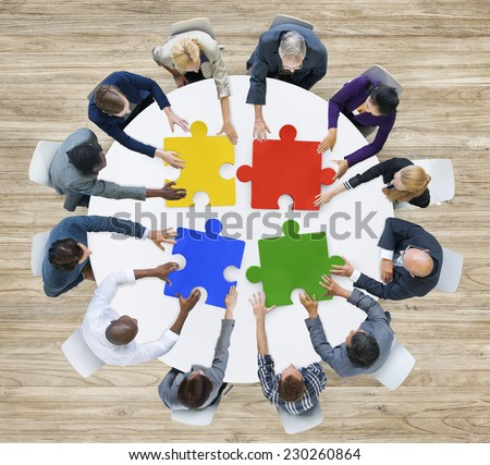 Business People with Puzzle Pieces and Teamwork Concept - stock photo
