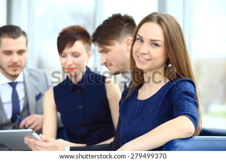 Business people with smiling female leader in foreground