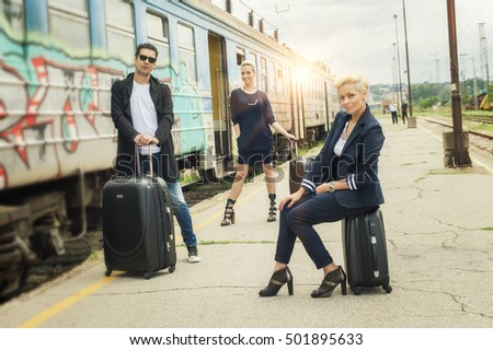 Business people with suitcase standing and posing on the railway station. Travel, trip, journey