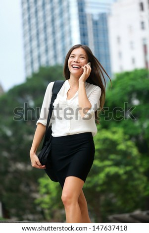 Business people - woman on smart phone, Hong Kong. Asian business woman office worker talking on smartphone smiling happy. Young multiracial Chinese Asian / Caucasian female professional in Hong Kong. - stock photo