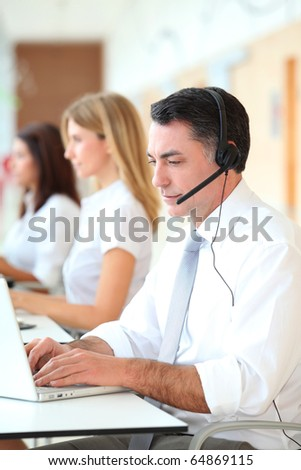 Business people working in front of computer with headphones - stock photo