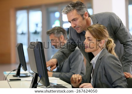 Business people working in office on desktop computer - stock photo