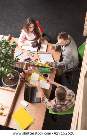 Business people working in overcrowded office and discussing business issues connected with their company, enterprise, firm, etc.
