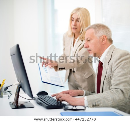 Business people working on a computer while reading a document in a bright office