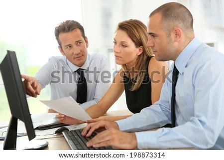 Business people working on desktop computer - stock photo