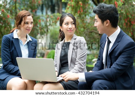 Business people working on laptop computer at outdoor