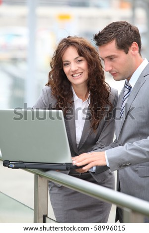 Business people working on laptop computer outside