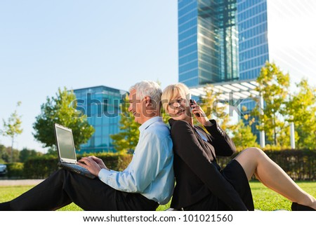 Business people working outdoors on a meadow - he is working with laptop, she is calling someone on phone - stock photo