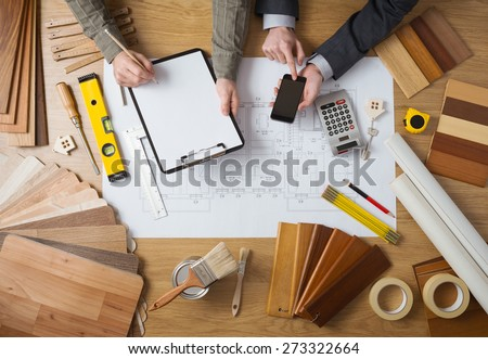 Business people working together on a building project, desktop top view with tools, wood swatches, mobile phone and blueprint - stock photo