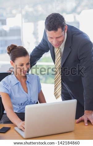 Business people working together on a laptop and smiling in the office - stock photo