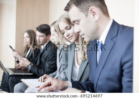 Business people working together sitting in a row in lobby and holding laptop and documents on knees