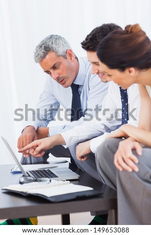 Business people working with their laptop on sofa at office - stock photo