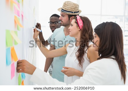 Business people writing ideas on sticky notes in the office - stock photo