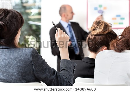 Business person asking a question at a meeting - stock photo