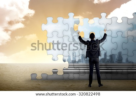 Business person building puzzle of city in the desert. Business building concept