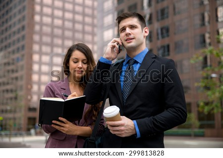 Business person CEO executive on cell phone walking near building with personal assistant - stock photo