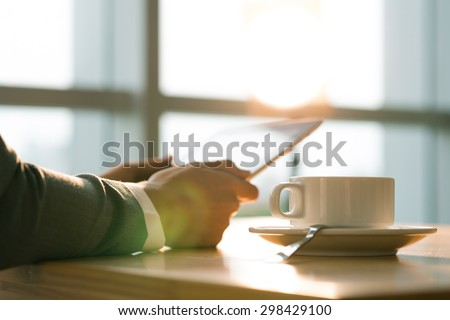 Business person drinking coffee and reading news on the digital tablet