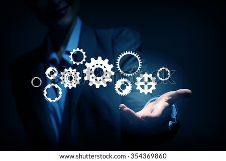 Business person hand holding gear mechanism representing interaction concept