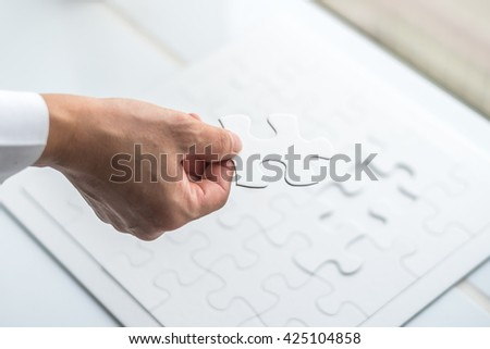 Business person hand placing missing a piece of puzzle together: Business team work company partner support concept: Cooperate for successful complete work: Problem solution solving creative idea - stock photo