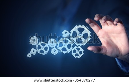 Business person hand touching gear mechanism representing interaction concept