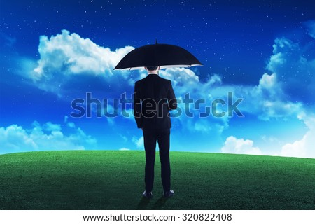 Business person holding umbrella on the grass at the night