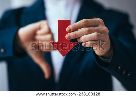Business person holds red arrow and shows thumb down - stock photo