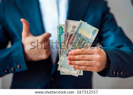 Business person holds roubles and shows thumb up