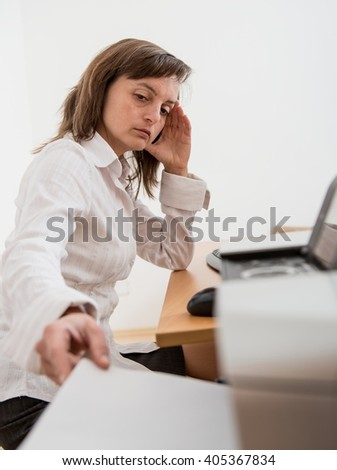 Business person in depression reaching hand and taking paper from printer on workplace - stock photo