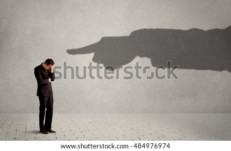 Business person looking at huge shadow hand pointing at him concept on background
